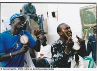 Un joven Yatma Thiam (derecha) tocando tama en un sabar particular en una casa de Dakar